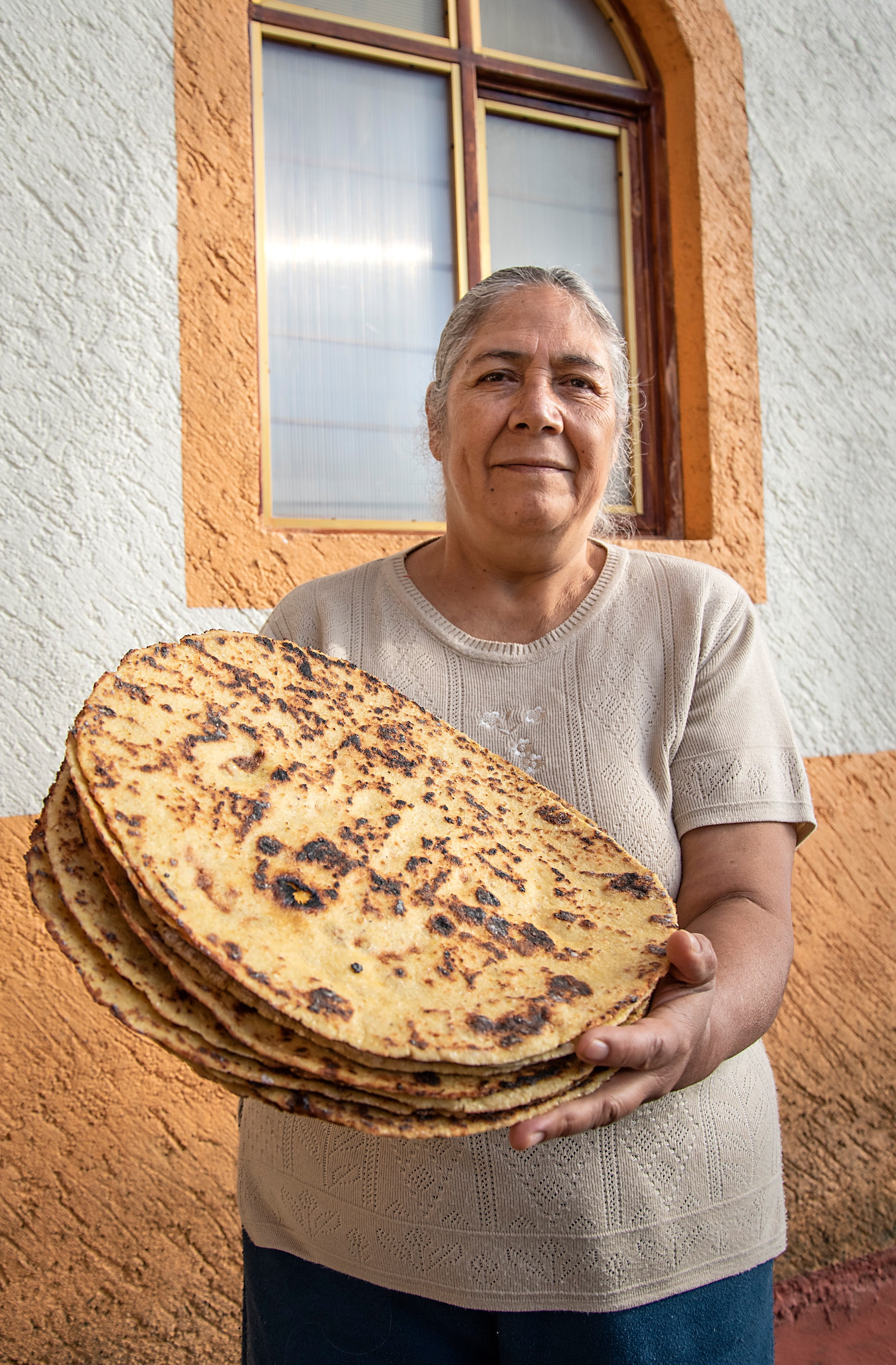 Woman posing with tortillas made from local maize
