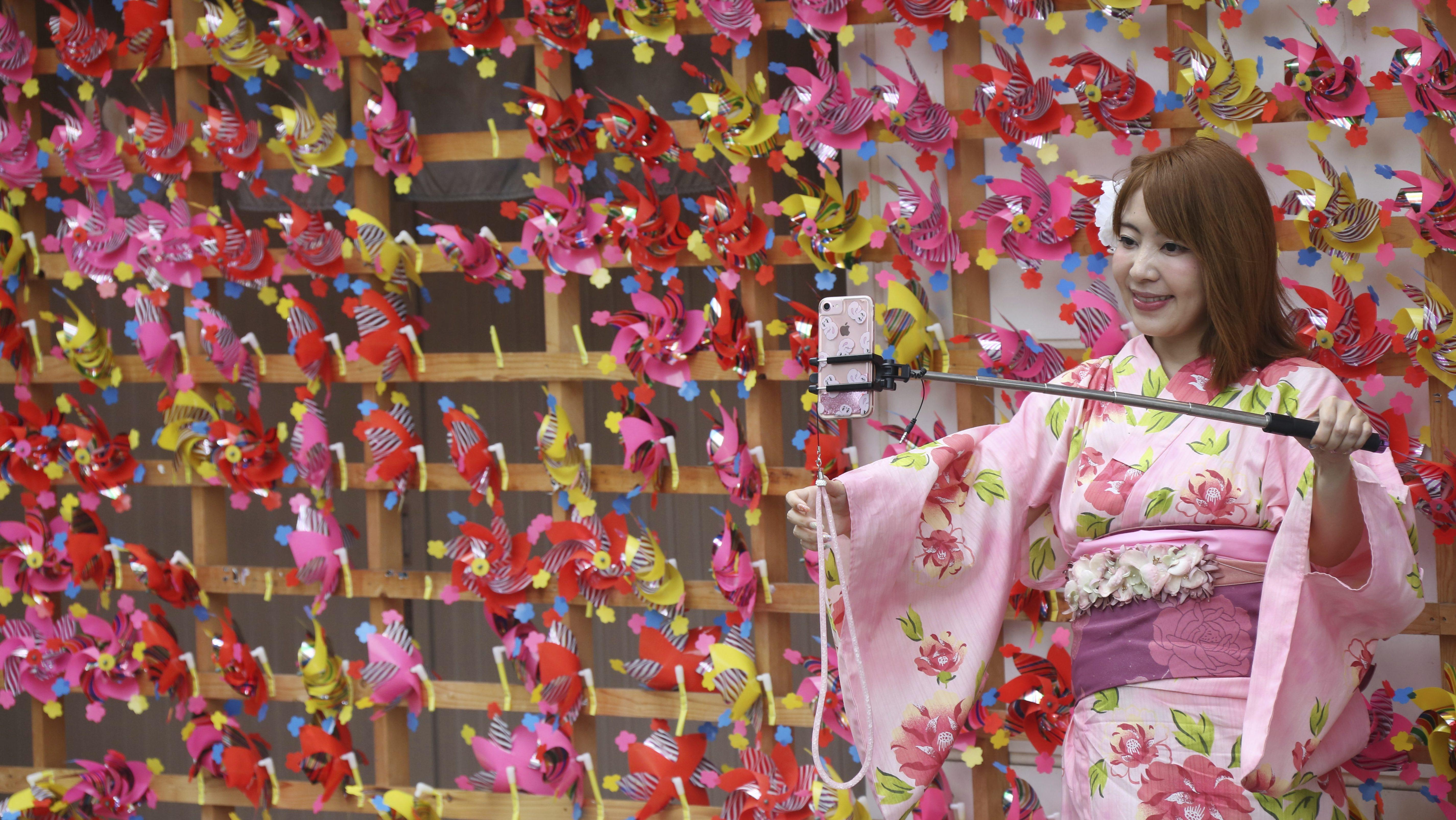 """A tourist clad in traditional Japanese summer kimonos or """"yukata"""" takes a selfie with pinwheels at Asakusa district n Tokyo, Friday, Aug. 24, 2018. (AP Photo/Koji Sasahara)"""