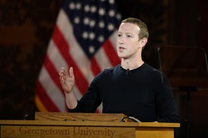 Facebook CEO Mark Zuckerberg speaks in front of an American flag.