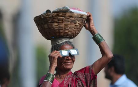 A roadside vender holding a basket on her head watches the eclipse in Hyderabad