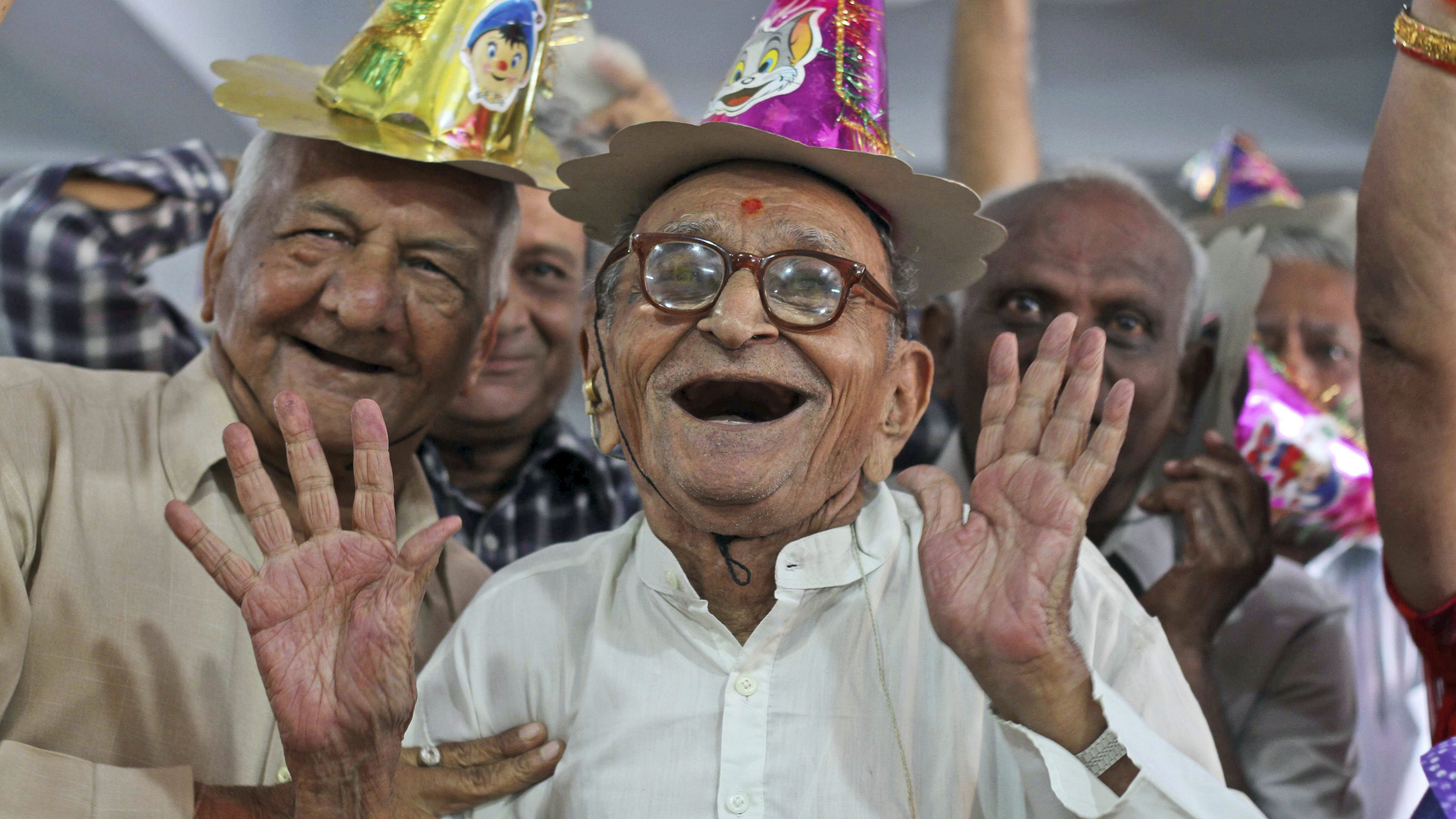 An elderly gentleman and his friends smile while wearing party hats at a celebration