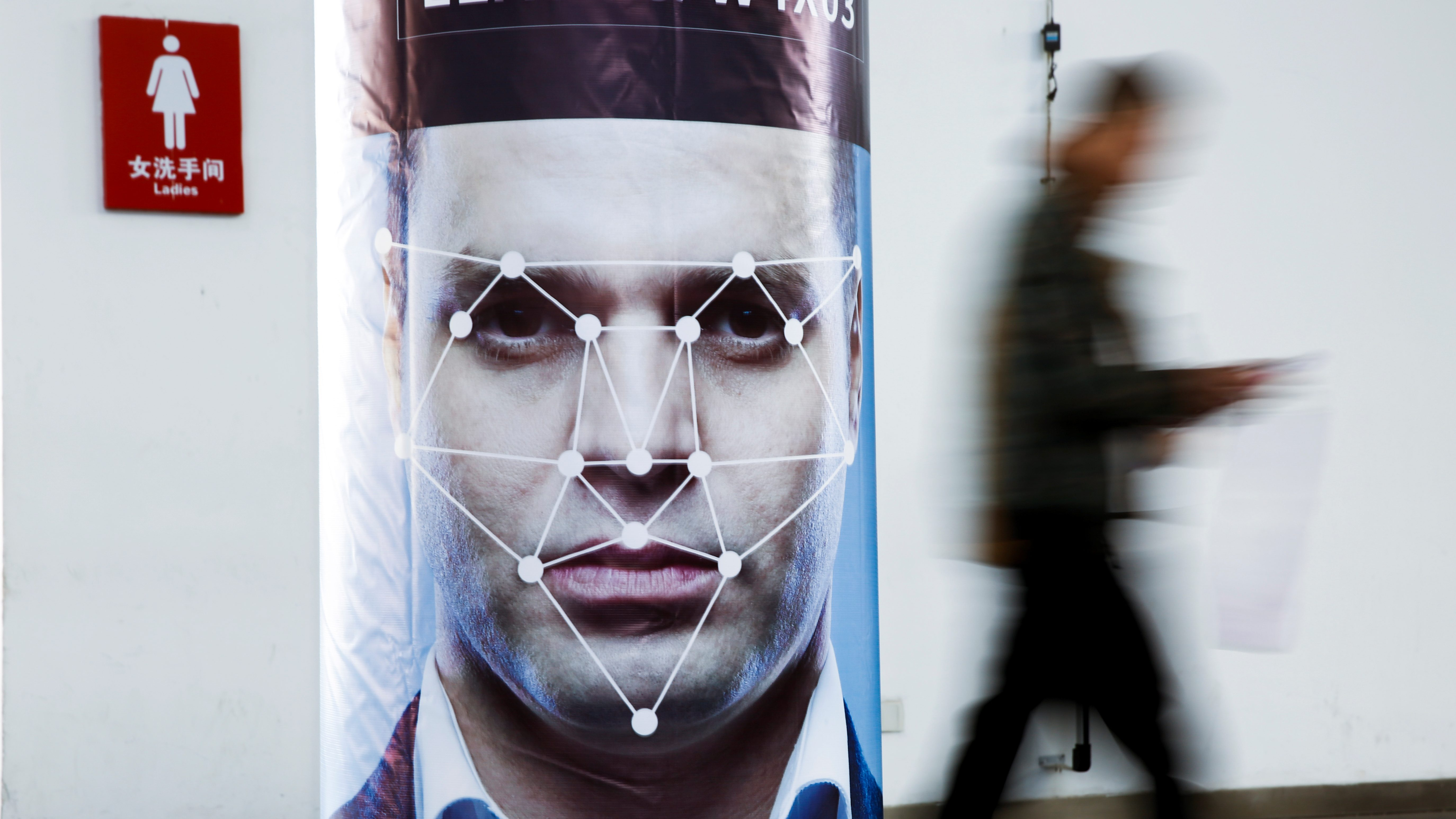 A man walks past a poster simulating facial recognition software