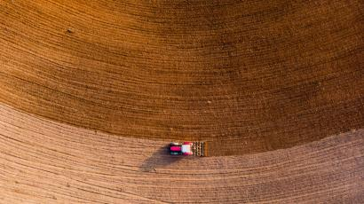 Aerial view with drone of tractor plowing the land in the countryside.