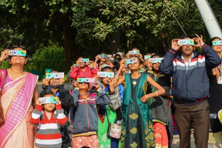 Students and teachers on the outskirts of Ahmedabad, India, watch the eclipse.