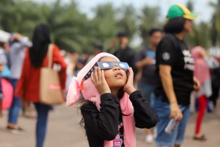 A young girl in Malaysia stares up at the eclipse