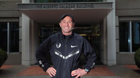 Alberto Salazar stands smiling with his hands on his hips.