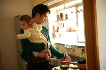 father cooking and holding his baby in the kitchen