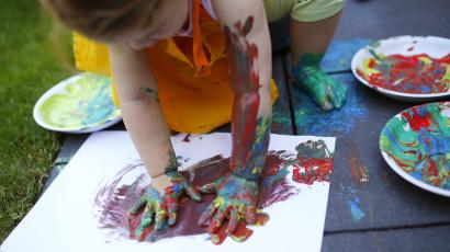 Two year-old Kaethe plays with paints in the garden of her home