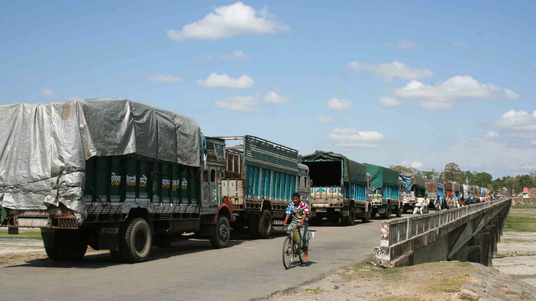 A Nepali man rides in front of trucks at the India-Nepal Panitanki border in eastern Nepal