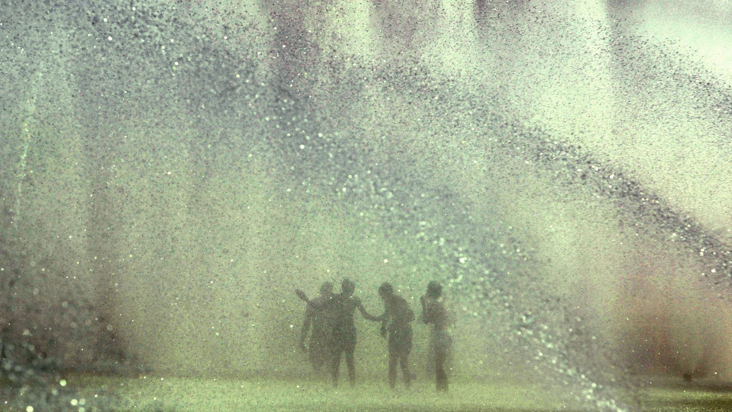 a fountain with eight shoots of water coming up and five blurry outlines of children playing in it.