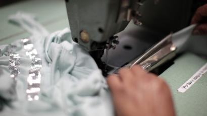 A worker sews clothes at a garment factory