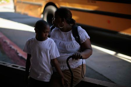 Black mother and son in front of school bus