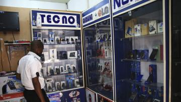 A man looks at smartphones on display at a shop at Wuse II business district in Abuja