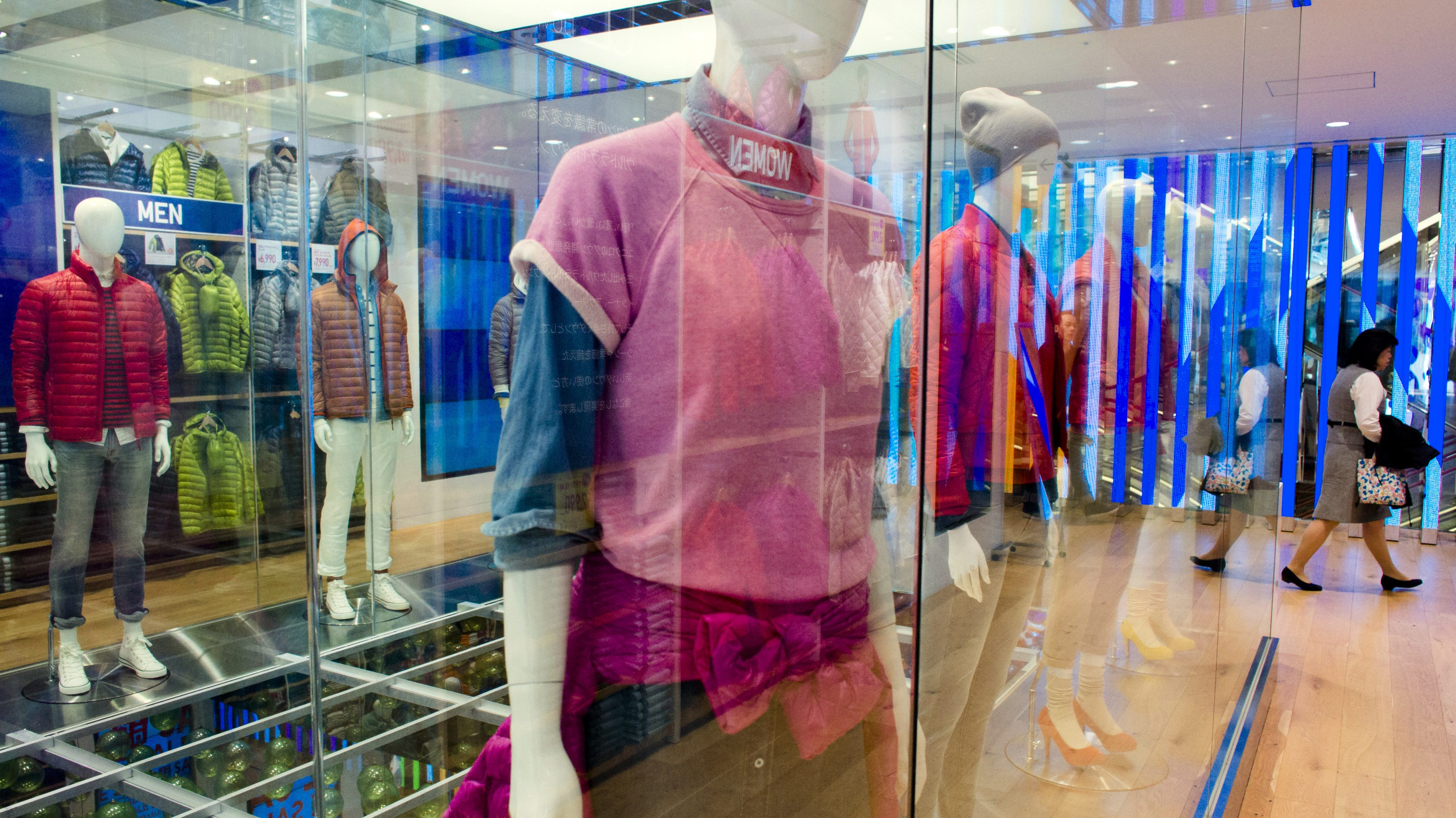 A woman walks past mannequins in brightly colored clothes