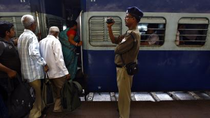 An Indian Railway police official films commuters as they board a passenger train at a railway station in Kolkata