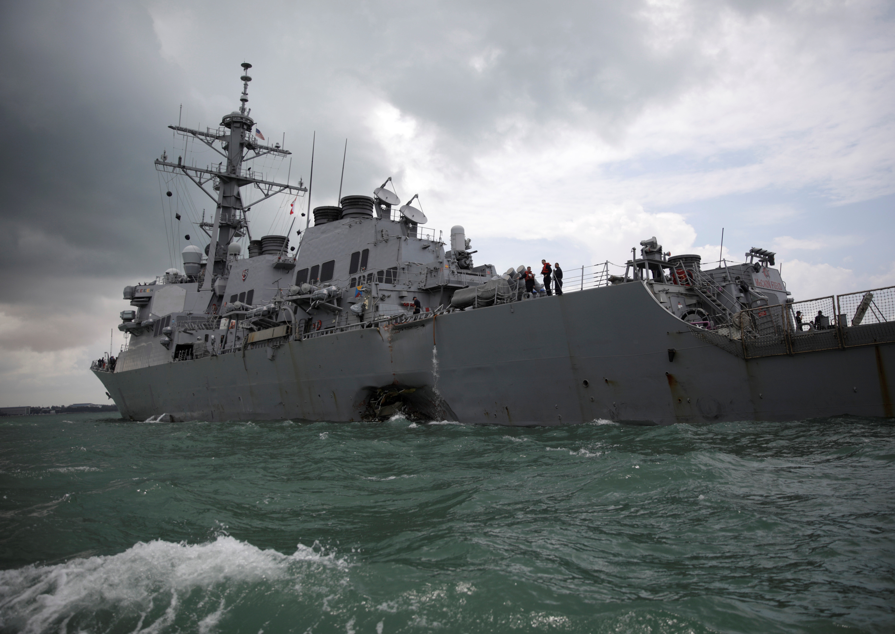 The U.S. Navy guided-missile destroyer USS John S. McCain is seen after a collision, listing and with a huge hole at the waterline.