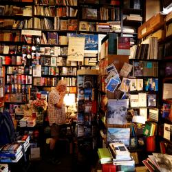A man looks at a shelf in a store crammed with books