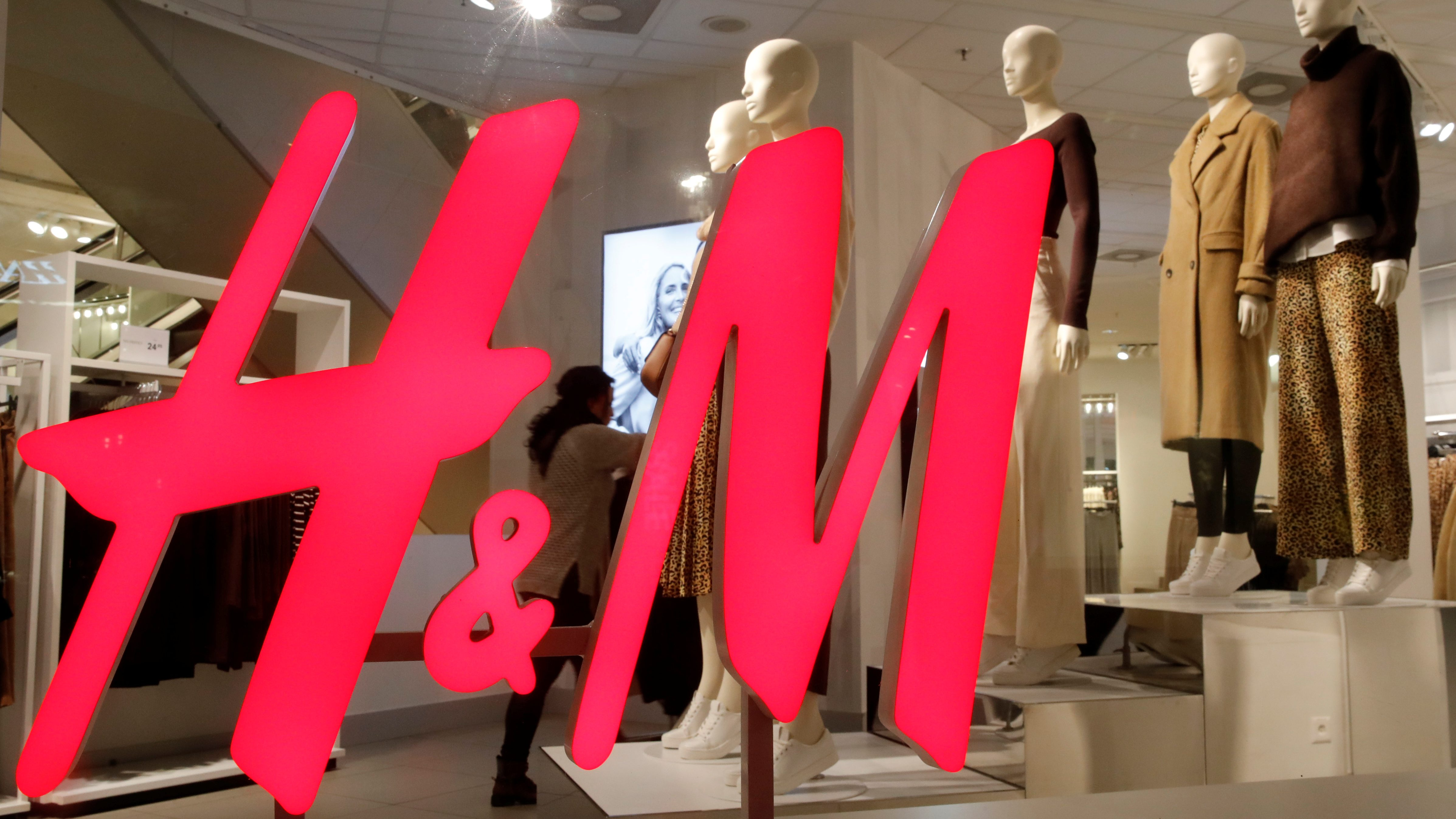 An H&M store window with the company's logo in the foreground and clothes in the background