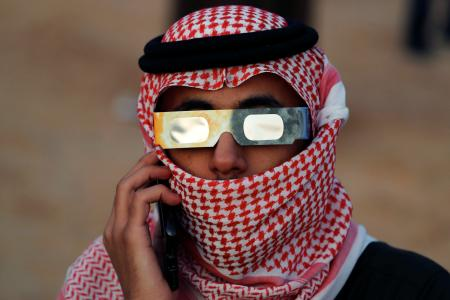 A Saudi man in red-and-white check head wrap watches the eclipse