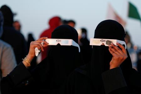 Saudi women holding protective glasses over black burkas that cover them completely watch the eclipse