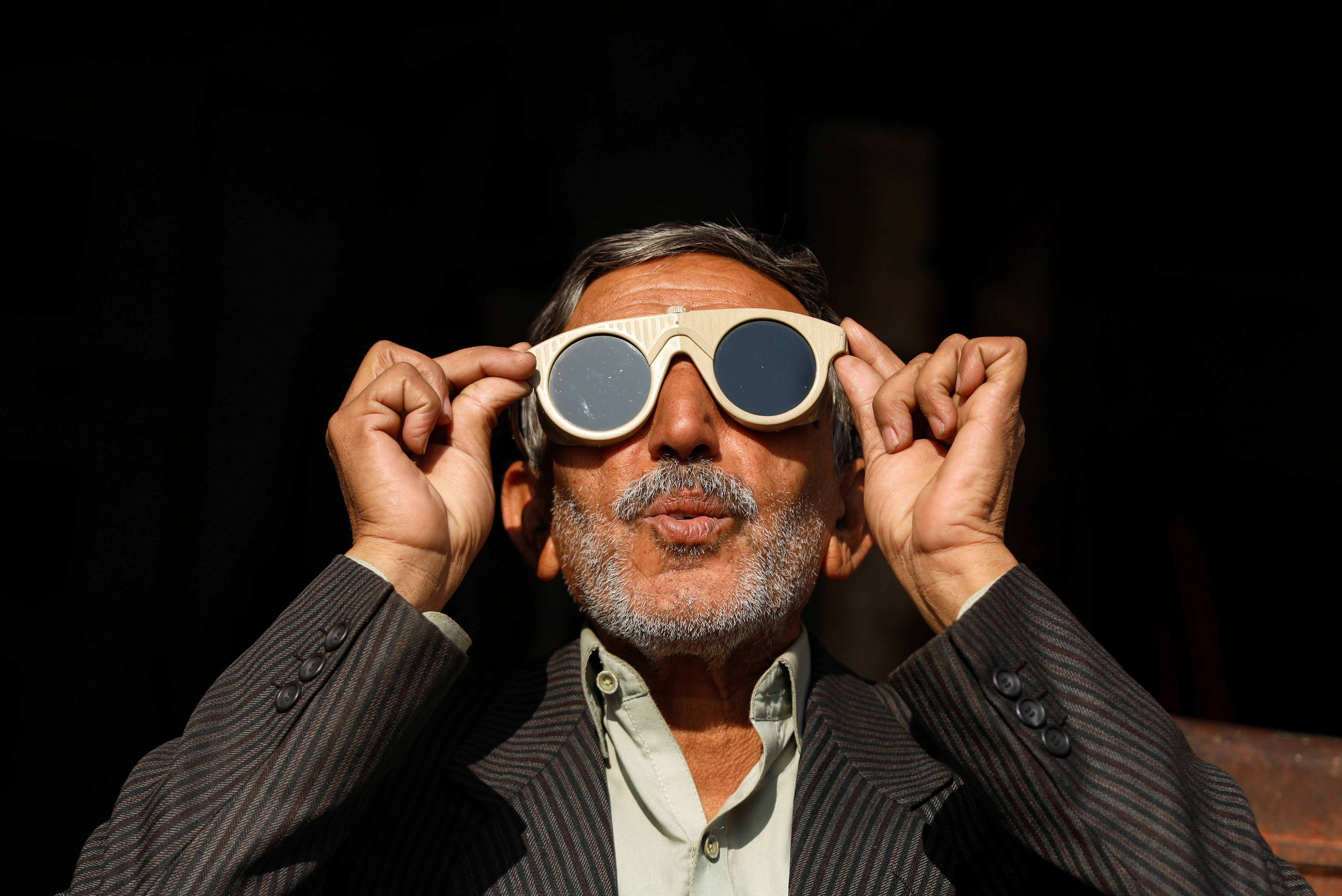 A man uses a pair of welder glasses to observe a solar eclipse in Peshawar, Pakistan