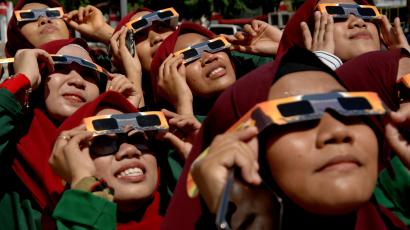A group of women in matching hijabs and protective glasses stare at the eclipse in Indonesia