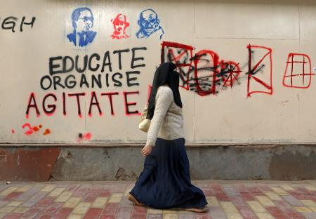A woman walks past a graffiti during a protest against a new citizenship law, outside the Jamia Millia Islamia university in New Delhi