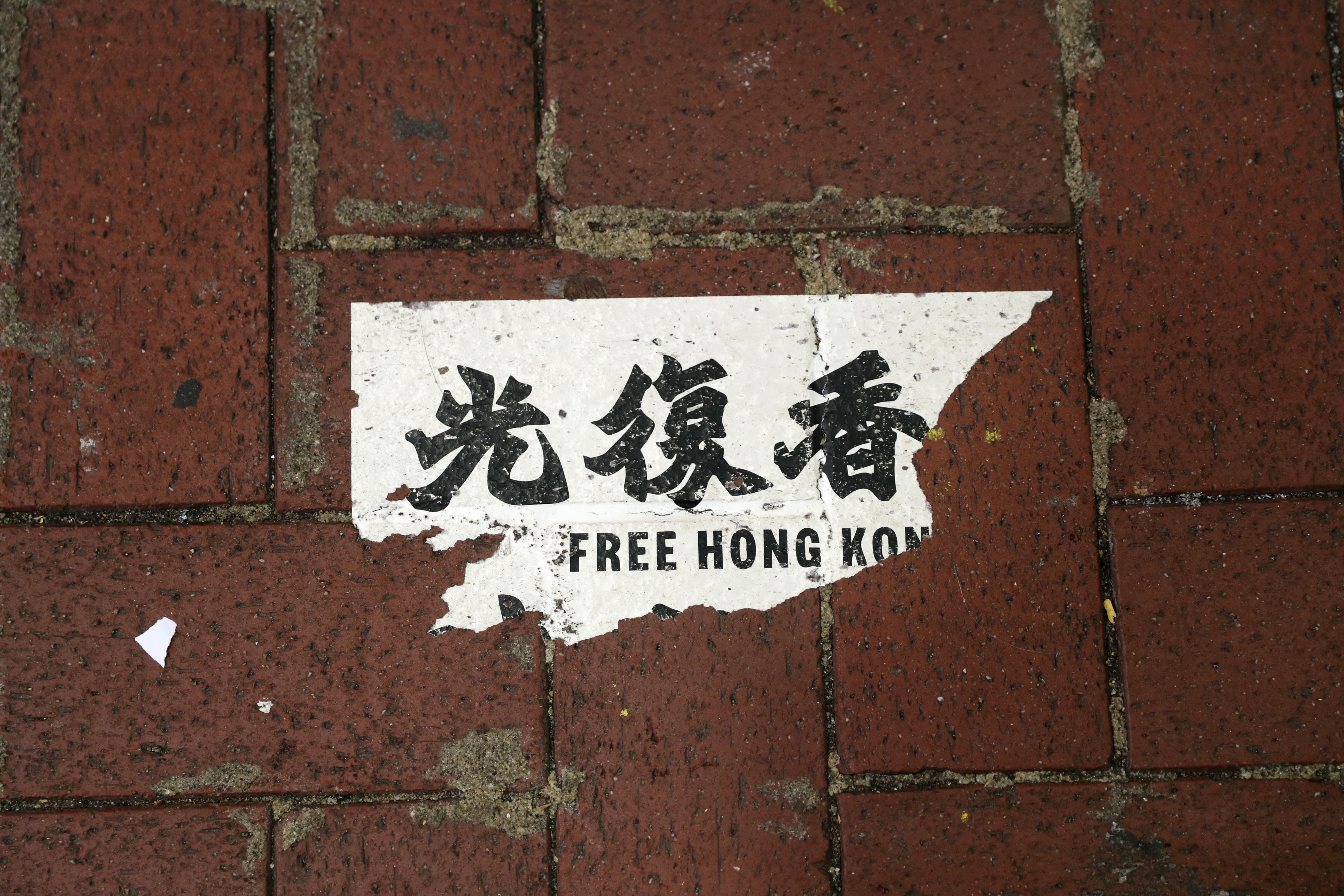 A Hong Kong protest sticker is seen on the sidewalk in Hong Kong