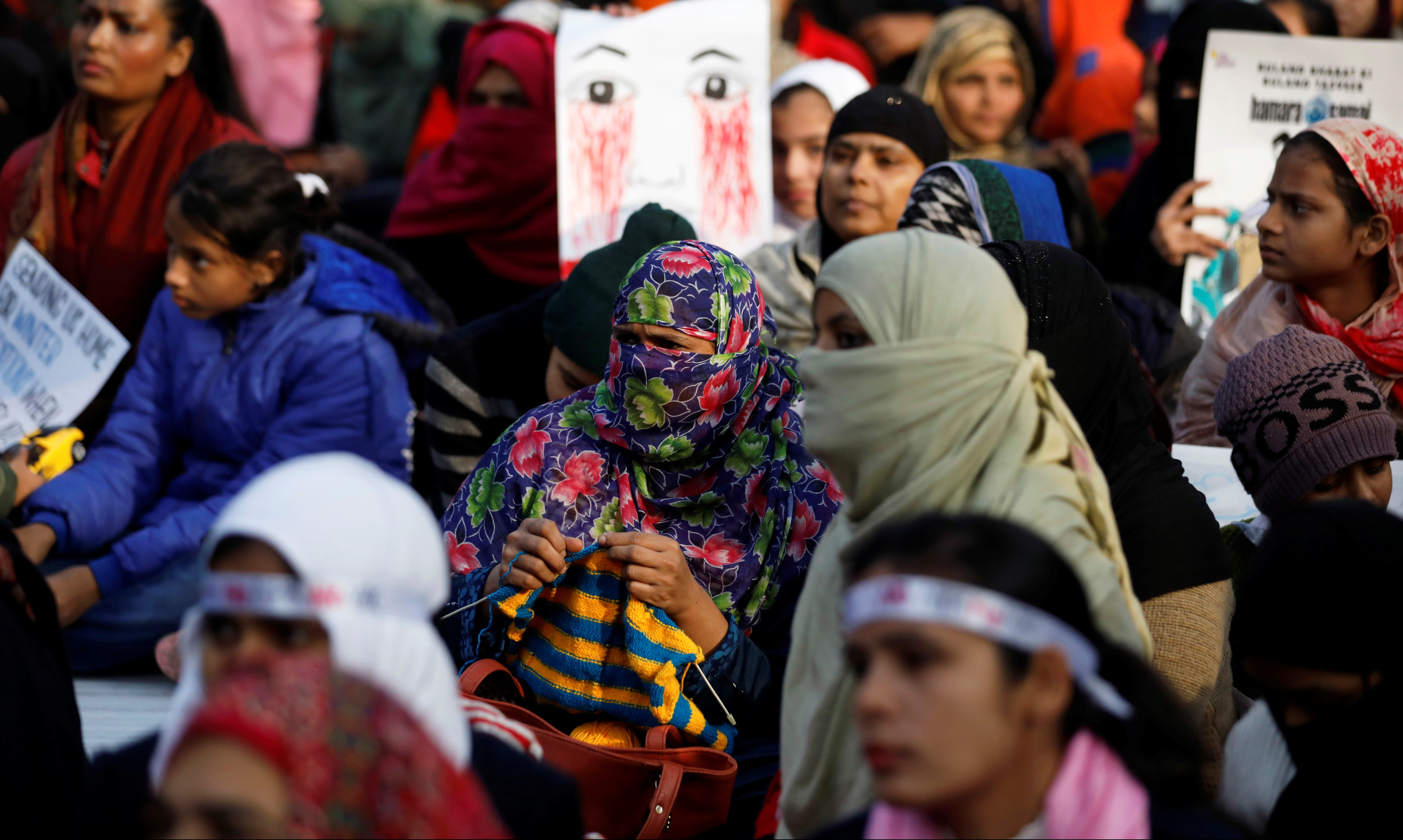 A woman knits as she attends a protest against a new citizenship law outside the Jamia Millia Islamia university in New Delhi
