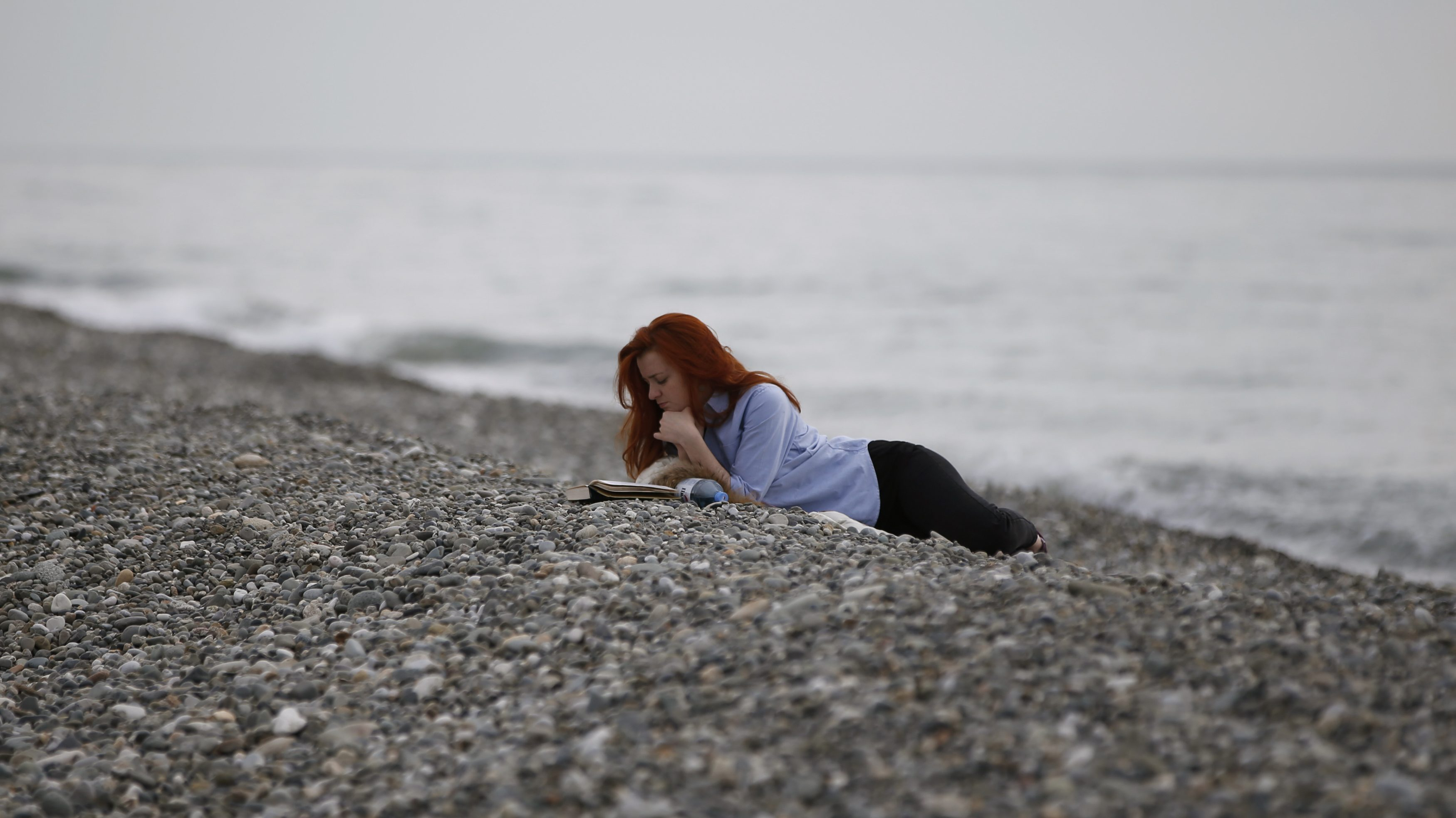 A woman reads a book on the beach at the Black Sea near the Olympic Park during the 2014 Sochi Winter Olympics