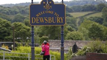 A woman walks past a sign welcoming visitors to Dewsbury in Yorkshire, northern England