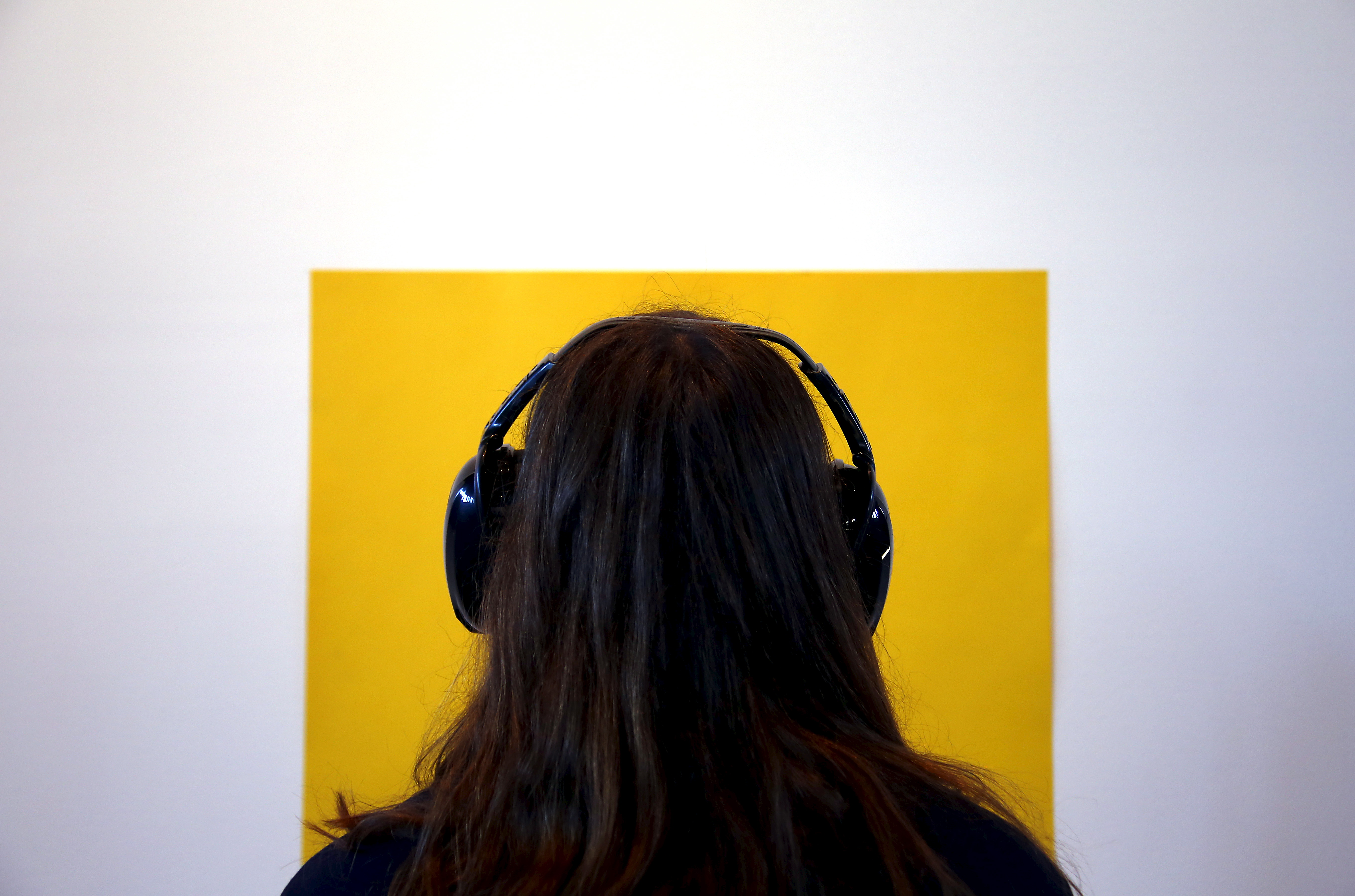 A museum visitor wearing noise-cancelling headphones.