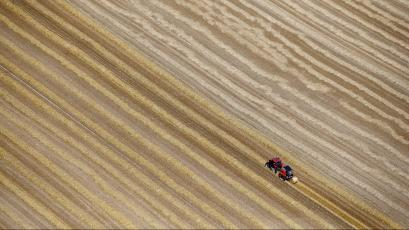 An aerial view shows a French farmer in his tractor making bales of straw after wheat harvest in his field in Coquelles near Calais