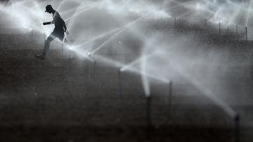 A worker makes his way through the water after setting up an irrigation system on an agricultural field, near Calexico, California,