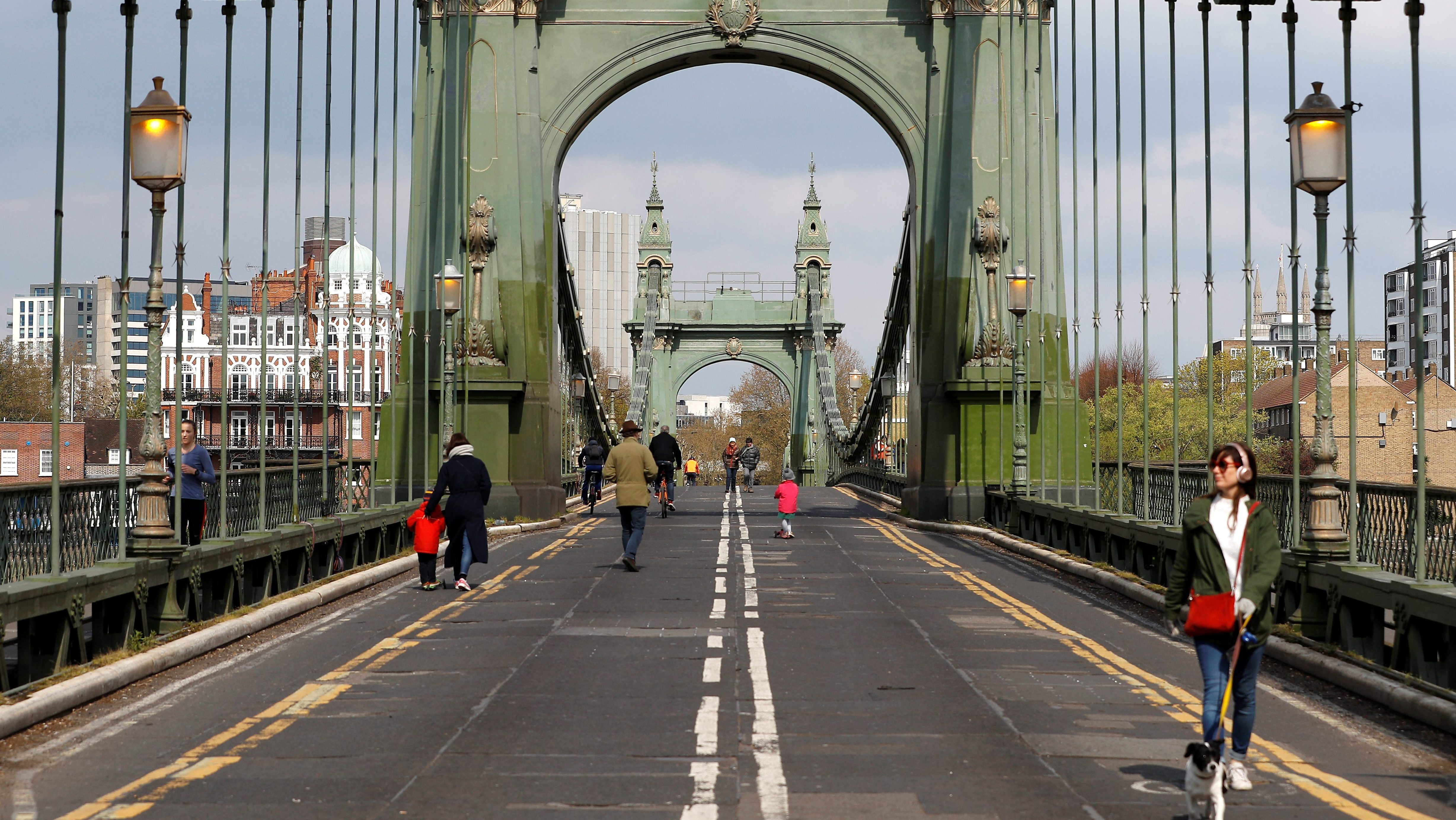Pedestrians walk across Hammersmith Bridge following its' closure to traffic caused by critical faults in London