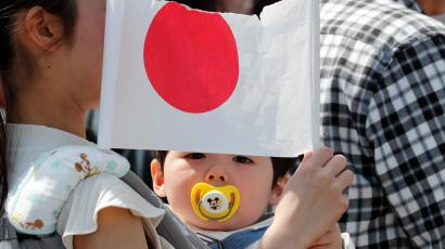 A baby holds a Japanese national flag outside the Imperial Palace