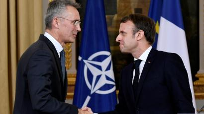 NATO Secretary General Jens Stoltenberg and French President Emmanuel Macron shake hands at the end of a news conference after their meeting at the Elysee palace in Paris
