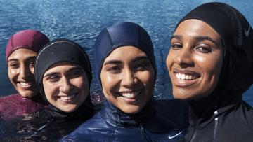 Four women in the water wearing Nike's Victory swimwear smile at the camera