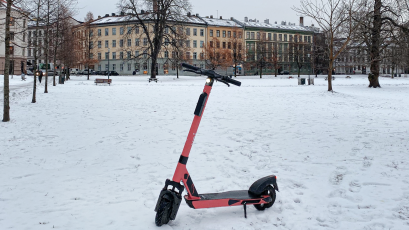 A Voi scooter parked in snowy Oslo.