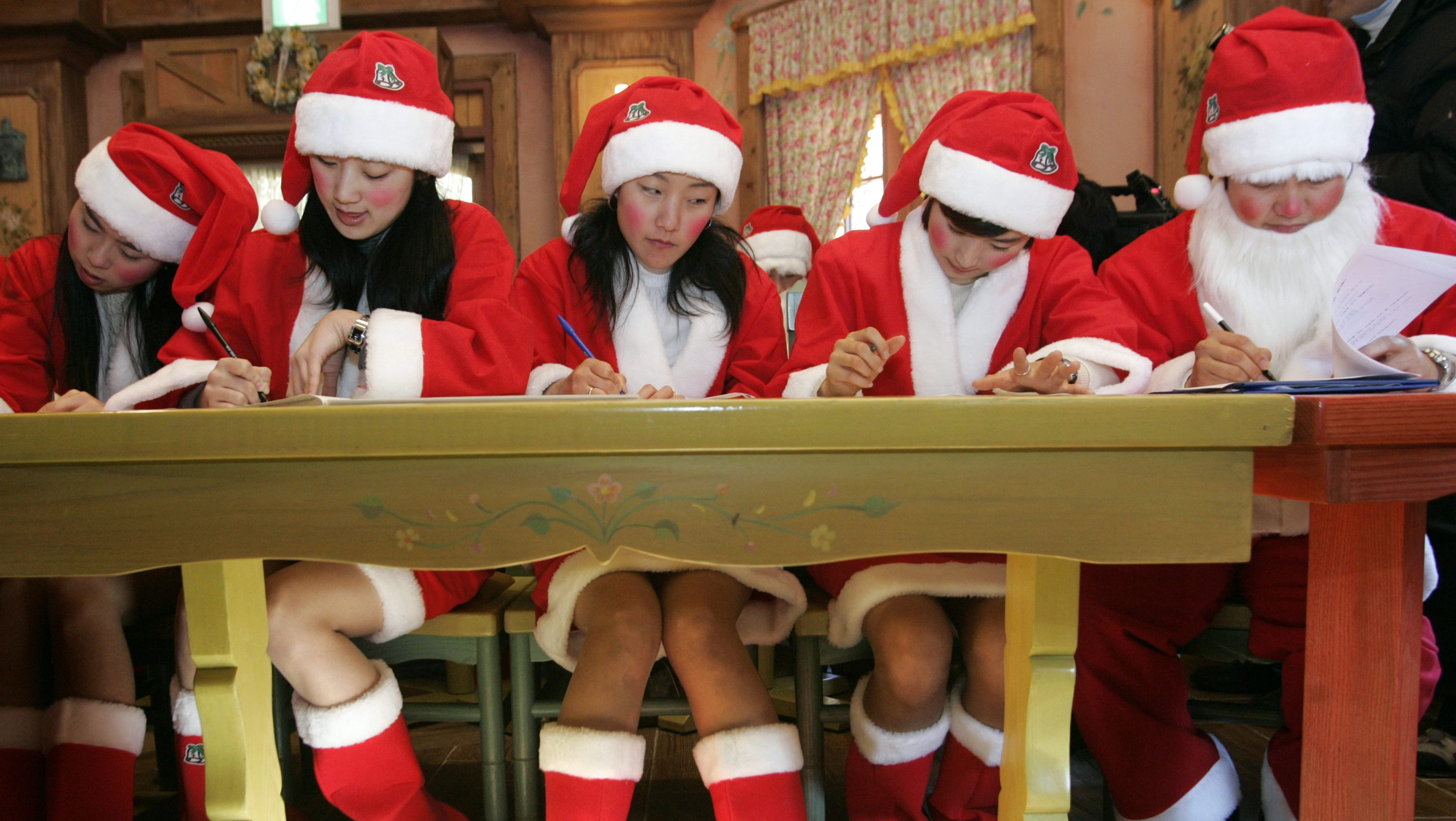 Kids study in Santa outfits.