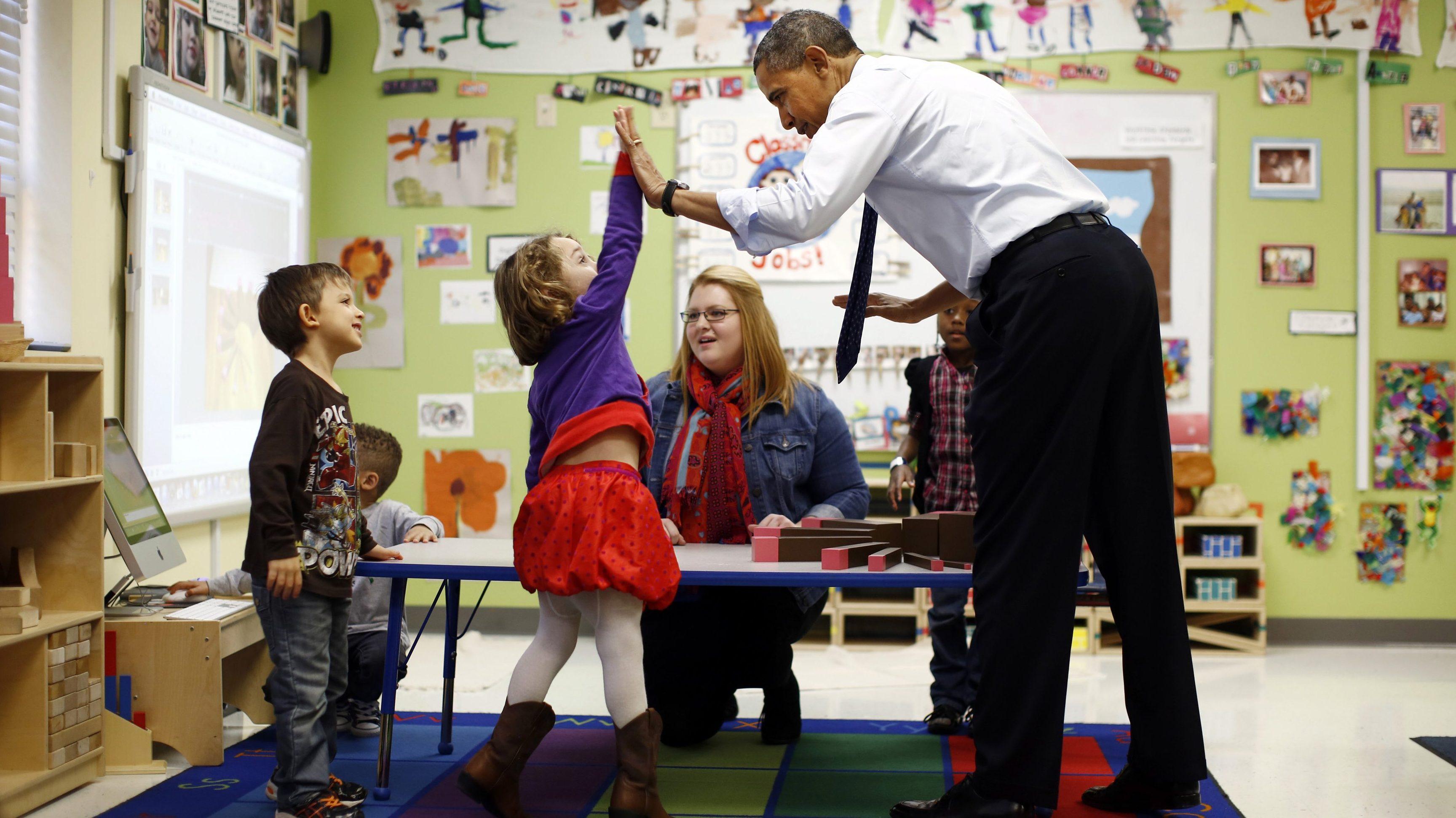 Barack Obama high-fives children in a pre-kindergarten classroom