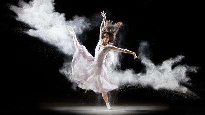 Ballerina performing in white powder in a dark room