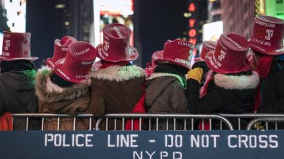 Revellers stand near a New York Police Department (NYPD) police cordon during New Year's Eve celebrations in Times Square, New York December 31, 2014.