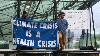 "Two members of the ""Doctors for Extinction Rebellion"" group hold up a sign that reads ""climate crisis is a health crisis."""