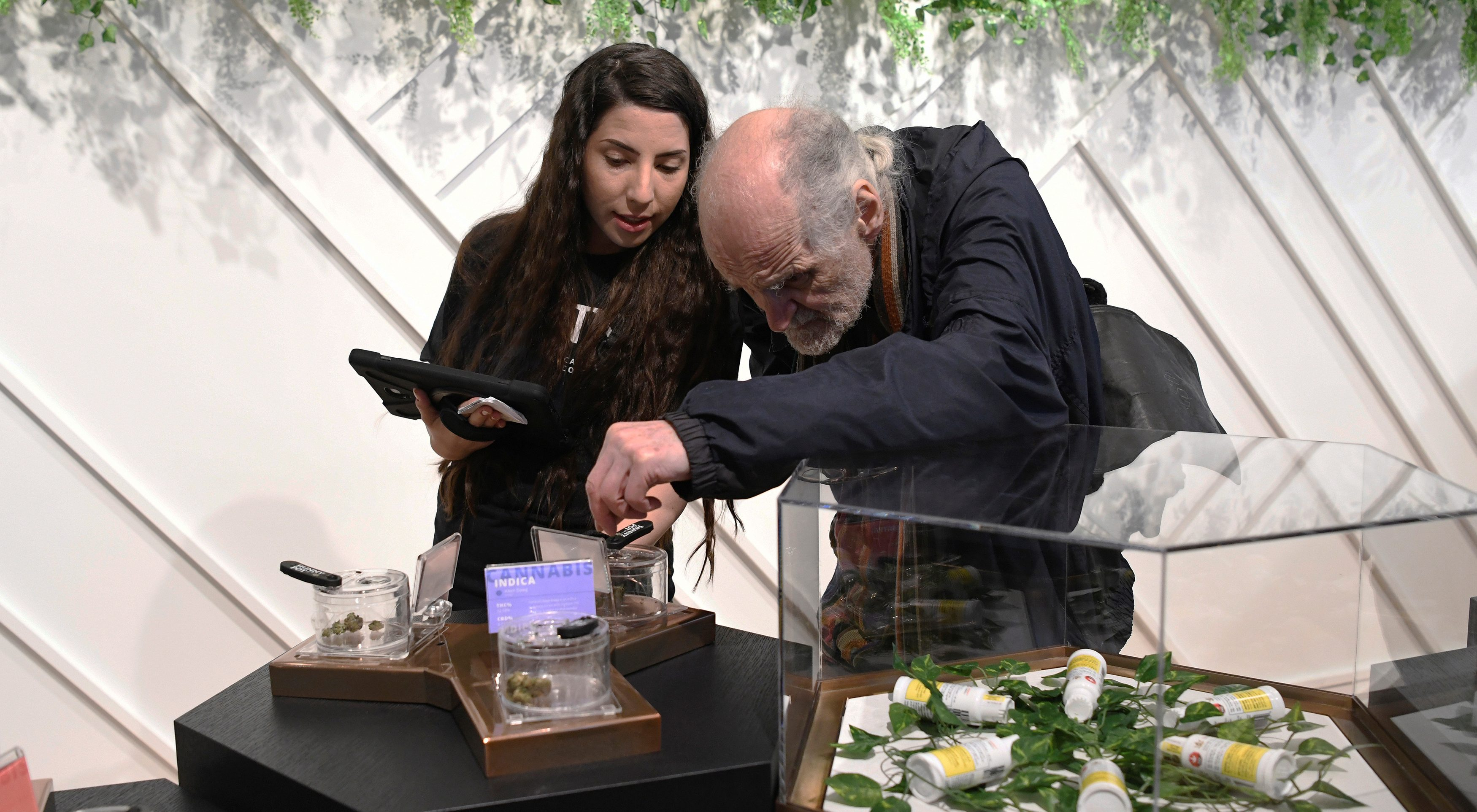 a customer and employee check out products at a cannabis dispensary