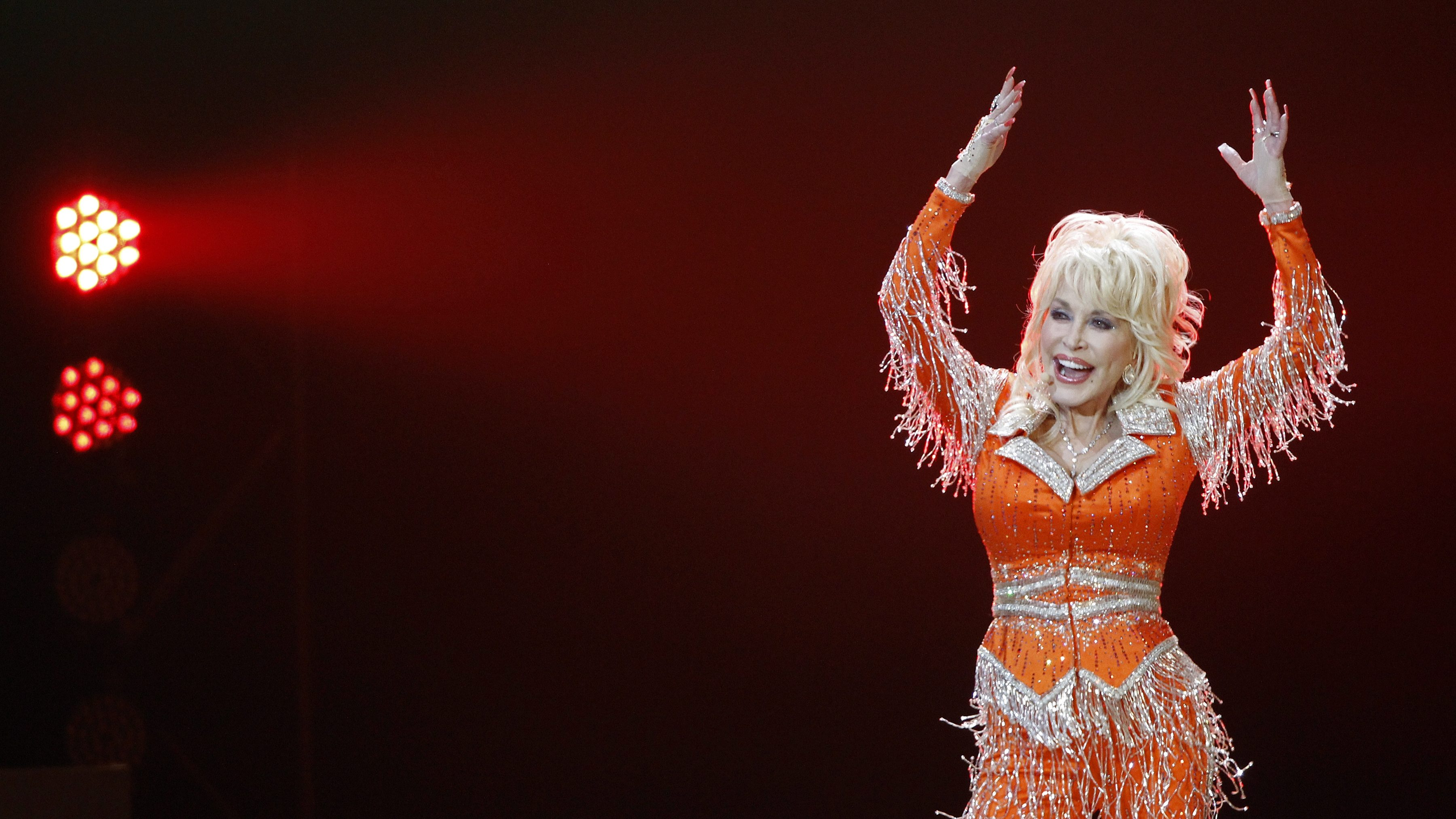 Photo of Dolly Parton in a brightly colored outfit with fringes. She's waving her hands up at a concert in 2014.
