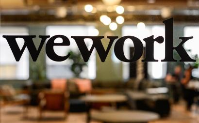 The WeWork logo on a glass office door.