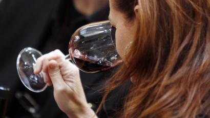 "A woman tastes a glass of Tuscan red wine on the opening day of the 44th edition of the annual International Wine and Spirits Exhibition ""Vinitaly"", in Verona, northern Italy, Thursday, April 8, 2010."