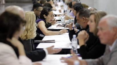 photo of job seekers talking to recruiters with resumes