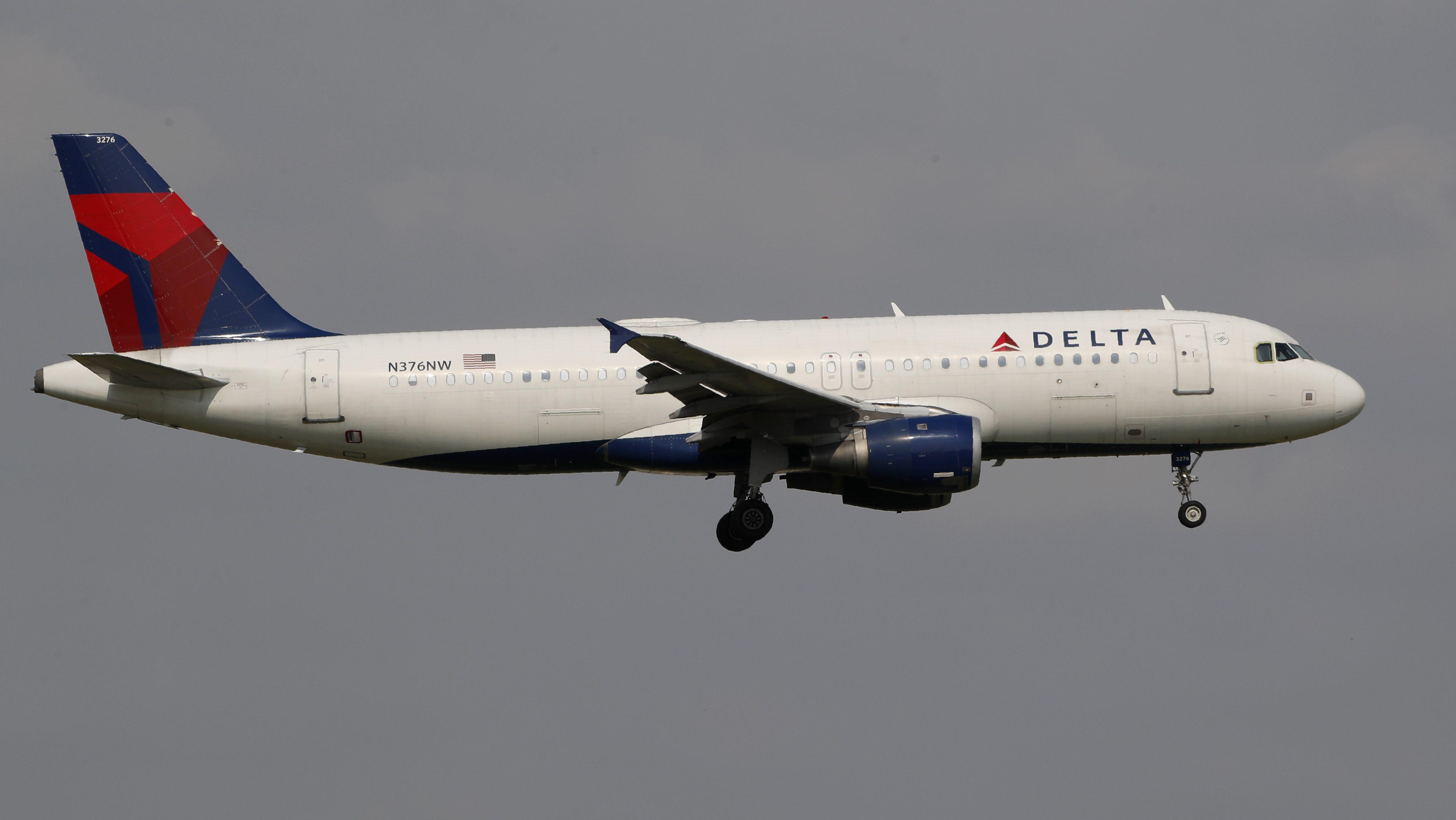 A Delta Air Lines flight against a grey sky.